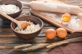 fresh cottage cheese, wheat ears, sour cream, eggs and flour on wooden table