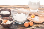 close-up view of cottage cheese, milk products, eggs and flour on wooden table