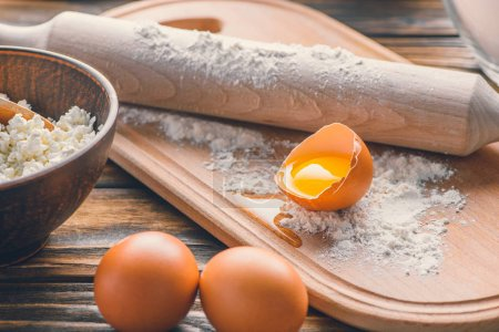 close-up view of raw eggs, flour with rolling pin and cottage cheese on wooden table