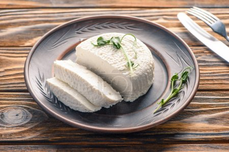 close-up view of tasty healthy soft cheese on plate on wooden table