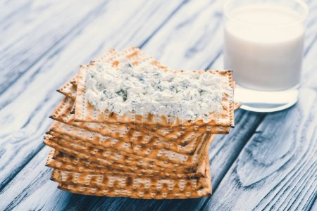 close-up view of crispy crackers with cottage cheese and glass of milk on wooden table