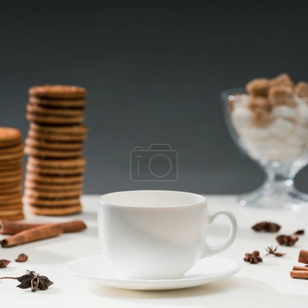 White cup for coffee on table with cookies and spices
