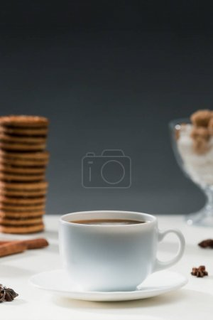 Hot black coffee in cup on table with cookies and spices
