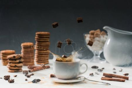 Photo for Coffee cup with splashing cane sugar on table with cookies and spices - Royalty Free Image