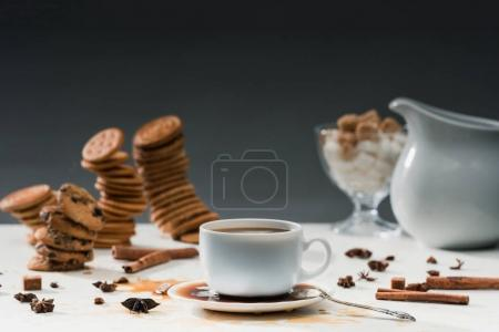 Cup with spilled coffee on table with biscuits and spices