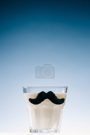 Transparent glass with mustaches filled with milk isolated on blue background