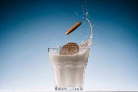 Sweet cookies splashing into glass of milk on blue background