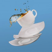 Black coffee in cup with saucers falling isolated on blue background