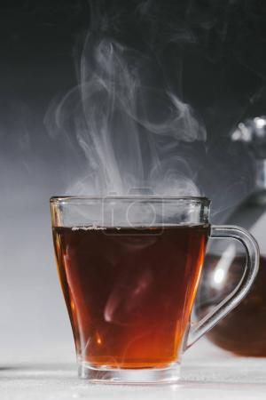 Photo for Steaming black tea in glass cup on table - Royalty Free Image