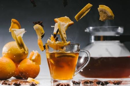 Glass cup of hot steaming tea with falling citrus pieces