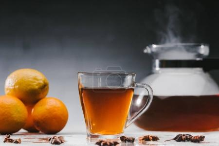 Photo for Cup of hot black tea with citrus fruits and steaming teapot - Royalty Free Image
