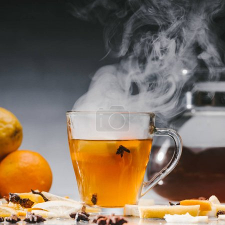 Steaming cup of hot black tea with citrus fruits