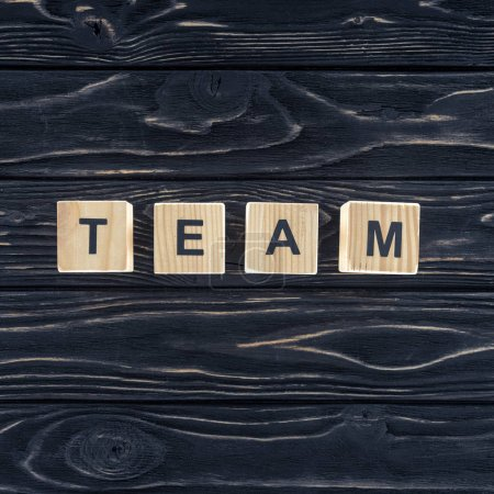top view of word team made of wooden blocks on dark wooden tabletop