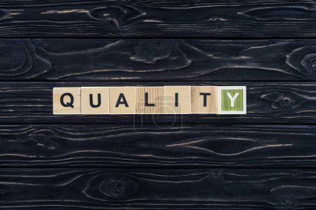 top view of word quality made of wooden blocks on dark wooden tabletop