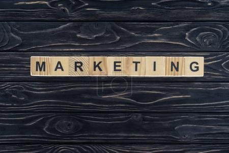 top view of word marketing made of wooden blocks on dark wooden tabletop