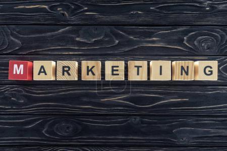 Photo pour Vue du dessus du marketing par mots en blocs de bois sur plateau en bois foncé - image libre de droit