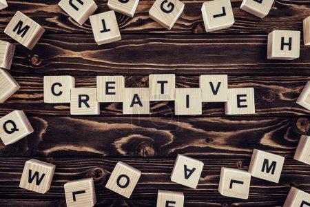 Photo pour Lay plat avec blocs disposés en parole créatrice sur une surface en bois brune - image libre de droit