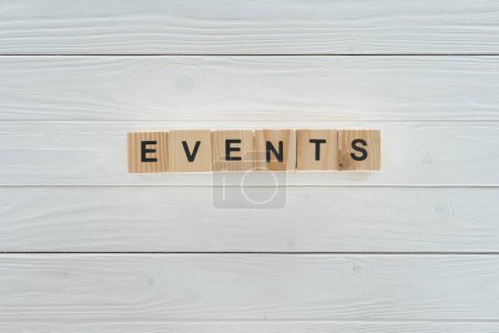 top view of events word made of wooden blocks on white wooden surface