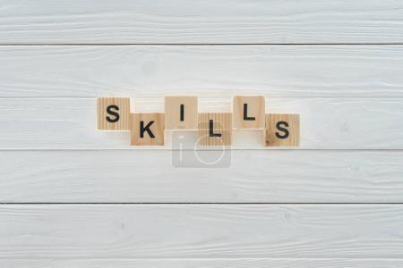 top view of skills inscription made of blocks on white wooden surface