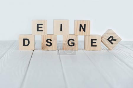 close up view of designer word made of wooden cubes on white wooden tabletop