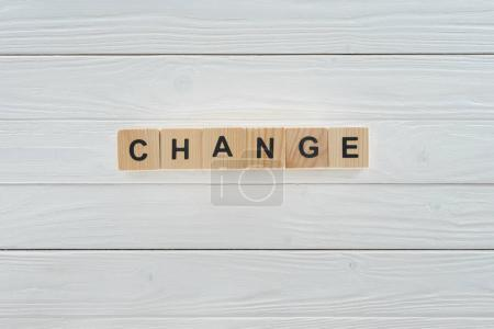 close up view of change word made of wooden cubes on white wooden tabletop