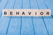 close up view of behavior word made of wooden blocks on blue tabletop