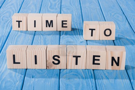 close up view of arranged wooden blocks into time to listen phrase on blue wooden surface