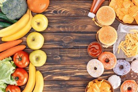 Photo pour Vue de dessus des fruits frais mûrs avec des légumes et de la malbouffe sur la table en bois - image libre de droit