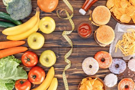 top view of assorted junk food, fresh fruits with vegetables and measuring tape on wooden table