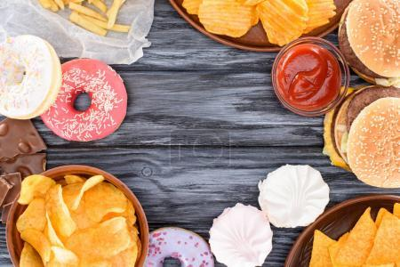top view of assorted sweets and junk food on wooden table
