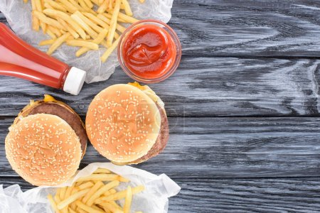 Photo for Top view of hamburgers with french fries and ketchup on wooden table - Royalty Free Image