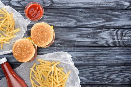 top view of hamburgers with french fries and ketchup on wooden table