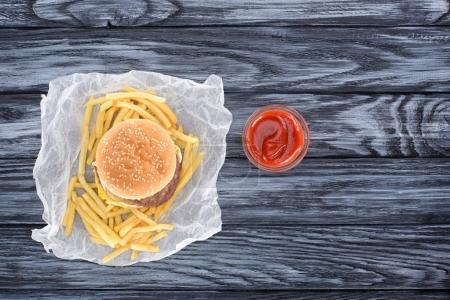 top view of hamburger with french fries and ketchup on wooden table