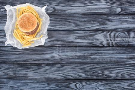 top view of hamburger with french fries on wooden table
