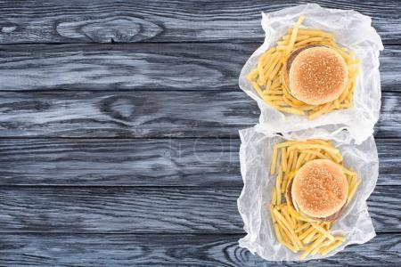 top view of two hamburgers with french fries on wooden table