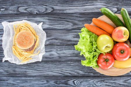 top view of hamburger with french fries and fresh fruits with vegetables on wooden table