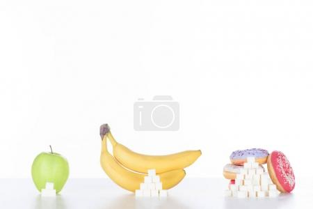 apple, bananas and doughnuts with sugar cubes on white