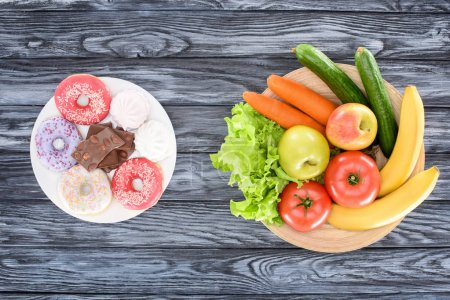 top view of fresh fruits with vegetables and sweets on wooden table