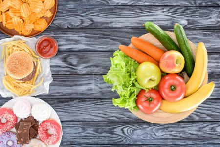 top view of fresh fruits with vegetables and plates with junk food on wooden table