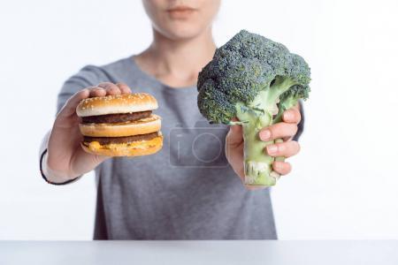 close-up view of woman holding fresh ripe broccoli and hamburger
