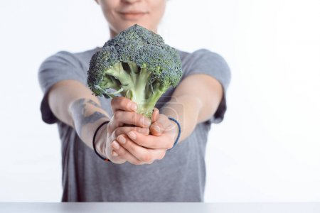 close-up view of woman holding fresh ripe broccoli