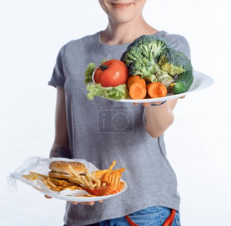 cropped shot of woman holding plates with vegetables and junk food