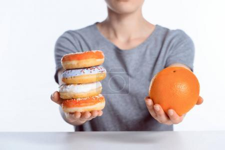 cropped shot of girl holding ripe orange and sweet donuts