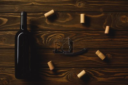 top view of bottle of red wine with corkscrew surrounded with corks on wooden table