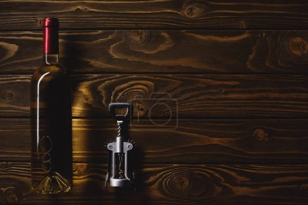 top view of bottle of luxury white wine and corkscrew on wooden table