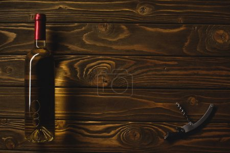top view of bottle of white wine and corkscrew on wooden table