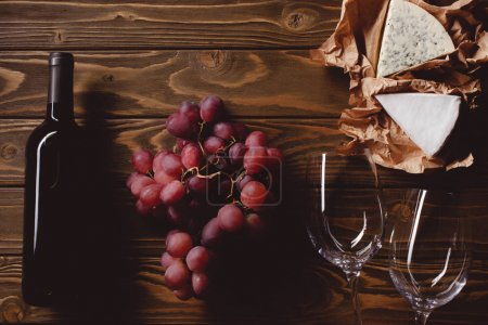 top view of bottle of red wine with glasses and appetizers on wooden table
