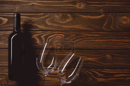 top view of bottle of red wine with empty glasses on wooden table