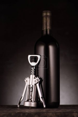 bottle of delicious red wine with corkscrew on black
