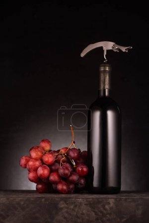 bottle of red wine pierced with corkscrew and grapes on black